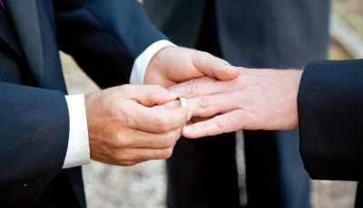 Gay couple exchanging rings at their wedding ceremony